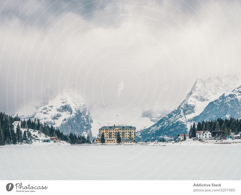 Beautiful building in snow surrounded by forest and mountains Building Mountain Forest Majestic Snow Landscape Winter Nature Vacation & Travel Sky Architecture