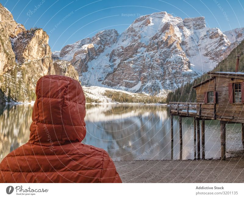 Unrecognizable person in warm jacket standing and looking at serene landscape Human being Landscape Serene Reflection Break water Nature Ocean Rock Coast Water