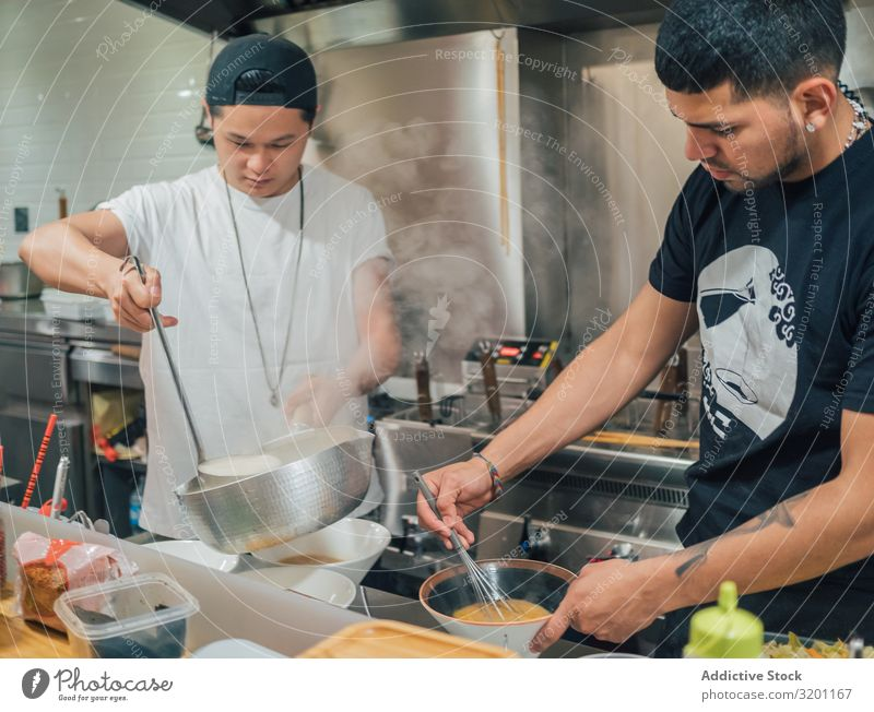 Asian males pouring soup in kitchen Man Cooking Soup Pot Food Japanese Dish Restaurant