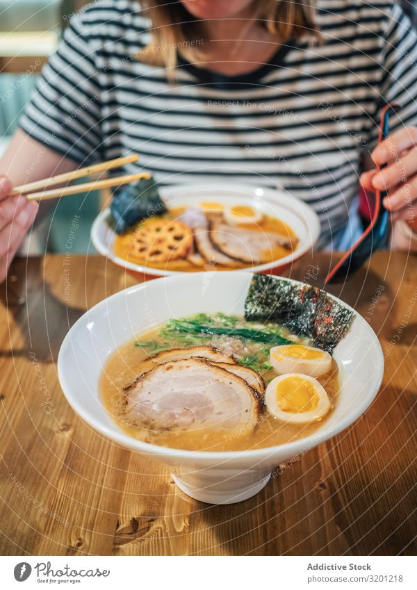 Female eating Japanese dish Woman ramen Soup Dish Bowl asian Food Tradition Lunch Dinner Human being Adults Eating Sit Hold enjoying Cooking Restaurant Meat Egg