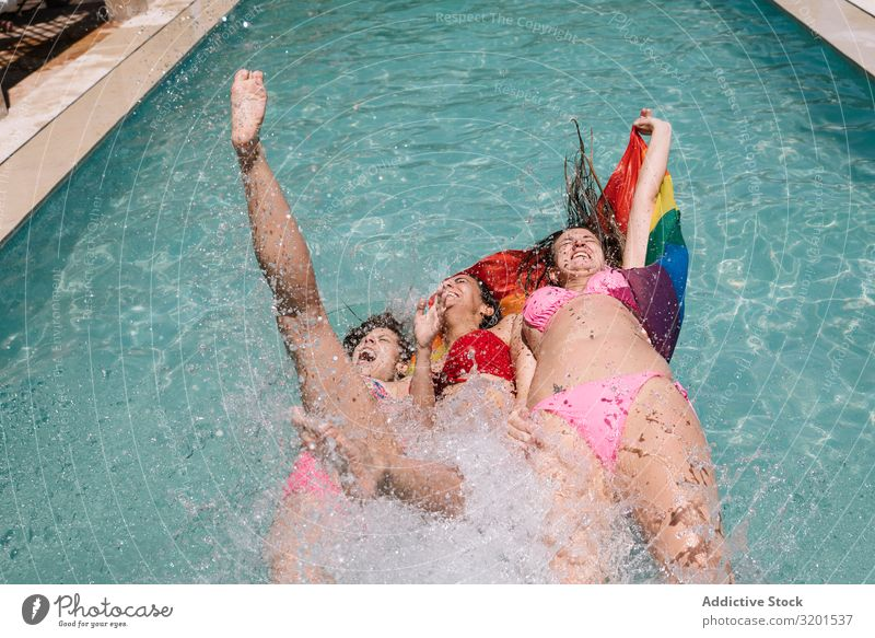 Anonymous lesbians splashing in swimming pool Swimming pool Splashing lgbt Flag falling Joy Barefoot Youth (Young adults) Woman Resort Vacation & Travel