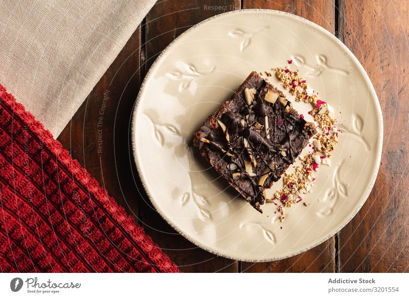 Tasty brown cake decorated with flakes on plate Cake Brown oat Natural Vegan diet vegan milk Food Dessert Fresh Delicious Wood Home-made appetizing Baking