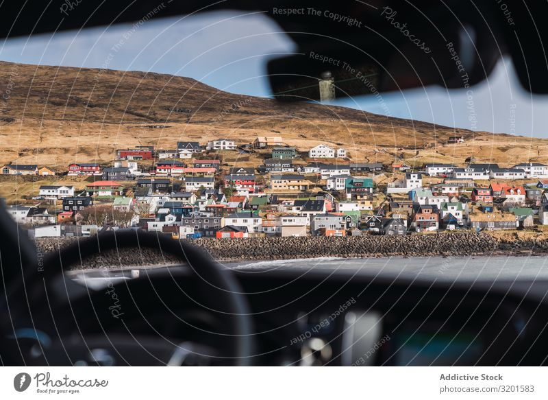 from car view of a small colorful village in Faroe Islands Town Hill Landscape House (Residential Structure) Føroyar Exterior Weather Sky Settlement Village