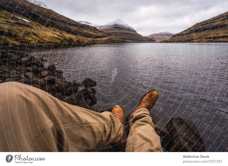 unrecognizable person sitting near lake showing legs Human being Legs Plant Coast Water Rock Stone Vantage point Picturesque Vacation & Travel Nature Sunlight