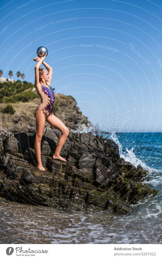 Female gymnast sitting on rocks and practicing Gymnast Woman rhythmic Athlete Ball Practice Gymnastics Sports Youth (Young adults) Human being Athletic Healthy