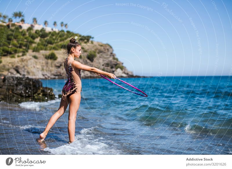 Graceful acrobat performs with hoop on beach Gymnast Woman rhythmic String Athlete Practice Gymnastics Sports Youth (Young adults) Human being Athletic artistic