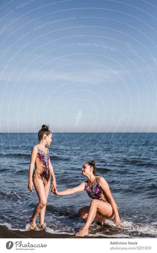 Female gymnasts holding hands on sea background Woman Gymnast rhythmic Athlete Sports pose Gymnastics Youth (Young adults) Girl Human being Athletic Thin