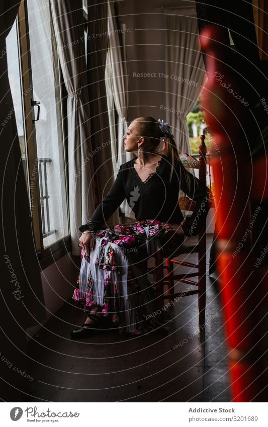 Woman dancer in suit for flamenco sitting and looking out window Dancer Dress Beautiful Expression To enjoy Flamenco Attractive Elegant Spanish Tradition