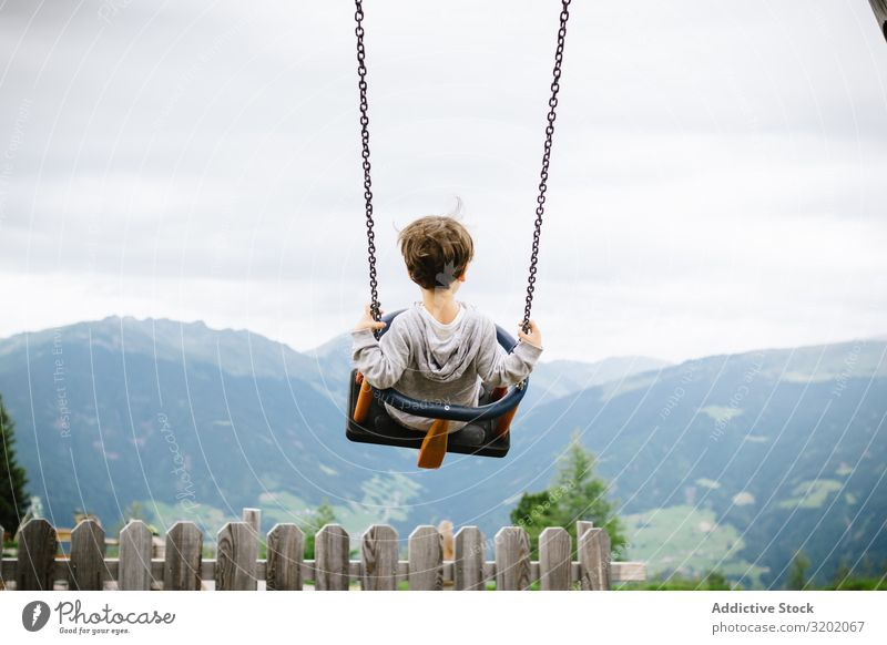 Child riding swings in cloudy day Flying Leisure and hobbies Cheerful Lifestyle Nature enjoyment Delightful amusement To swing Beautiful Sky Spinning Freedom