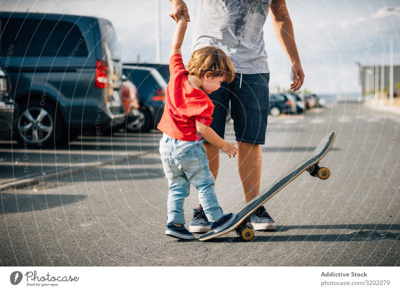Man with kid training with skateboard Father Child Skateboard enjoying parenthood Walking Vacation & Travel Family & Relations teaching Together Joy