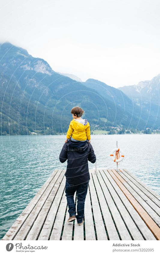 Man with kid on neck walking along pier Father Child parenthood Landscape Jetty Walking Nature Vacation & Travel Family & Relations Together Mountain