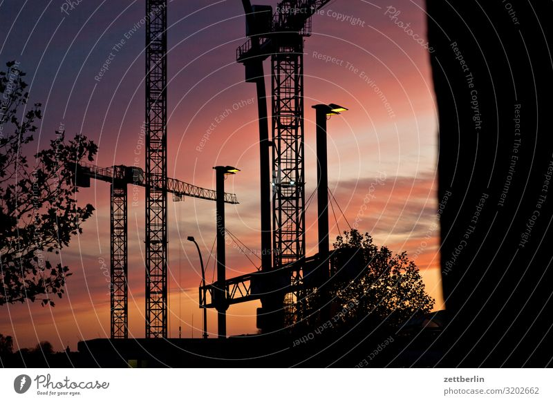 Construction site in the evening Evening slewing crane Dark Twilight Closing time Worm's-eye view large construction site Sky Heaven Industrial construction