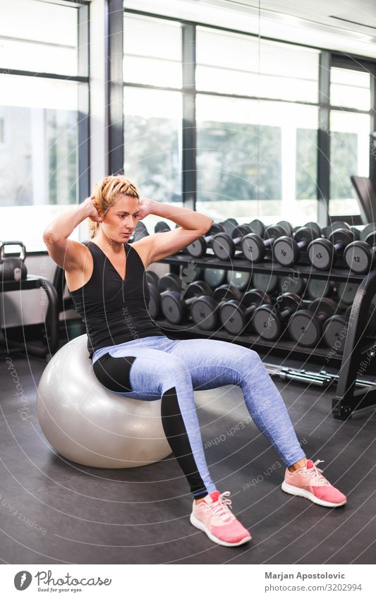 Young woman doing crunches on the ball in the gym Lifestyle Athletic Fitness Sports Sports Training Human being Feminine Youth (Young adults) Woman Adults 1