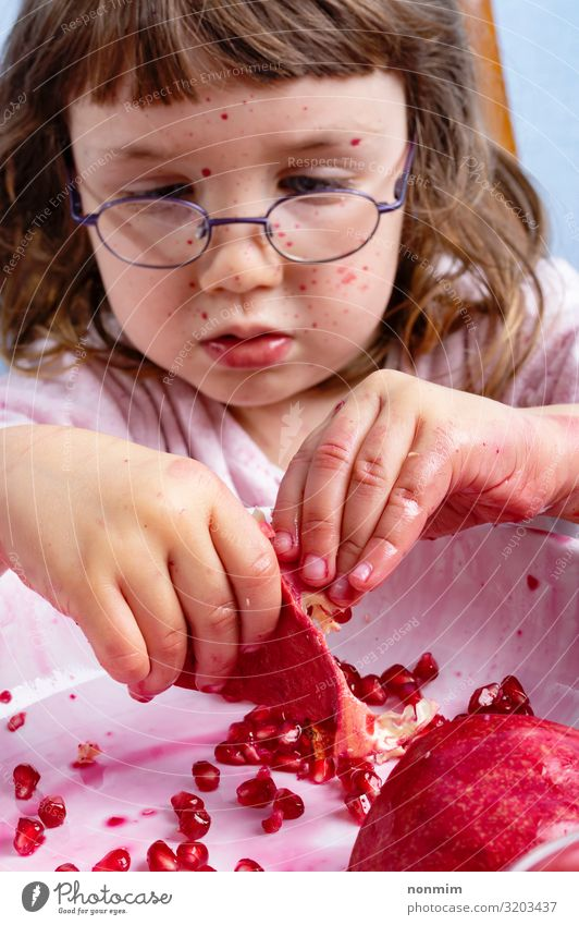 Girl peel pomegranate. Face dirty of red spots Fruit Dessert Nutrition Vegetarian diet Child Eyeglasses Dirty Fresh Natural Curiosity Juicy Red Concentrate