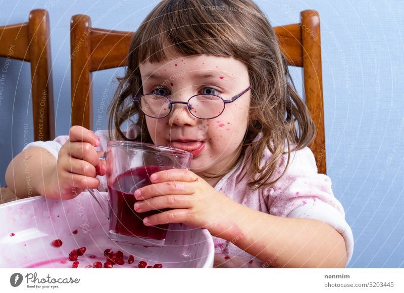 Girl tastes pomegranate juice. Face dirty of red spots Fruit Dessert Nutrition Vegetarian diet Diet Beverage Juice Lifestyle Exotic Joy Playing Child Infancy