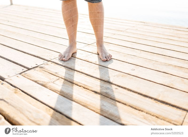 Legs of adult standing on wooden pier in sunlight Man Stand Jetty Feet crop view Summer Contentment body part Nature Leisure and hobbies Adults Sunbathing Water