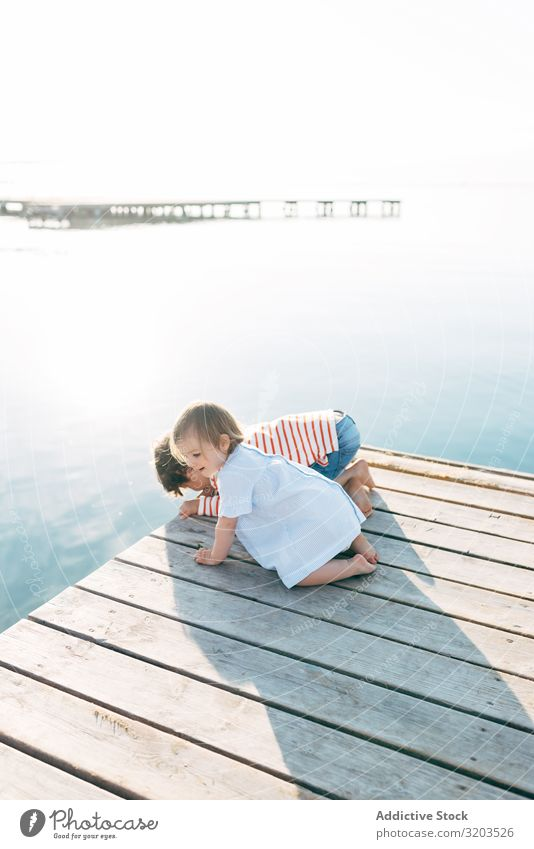 Curious kids on pier Child Strange seascape Jetty Together Observe Cute Baby sibling Boy (child) Girl Charming Sit Vacation & Travel Family & Relations Brother