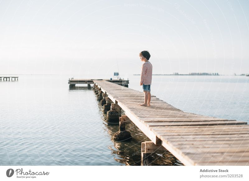 Lonely kid on pier in sunshine Boy (child) Jetty Dream Child Summer Sunlight Vacation & Travel Infancy Water Nature Leisure and hobbies Trip Intellect