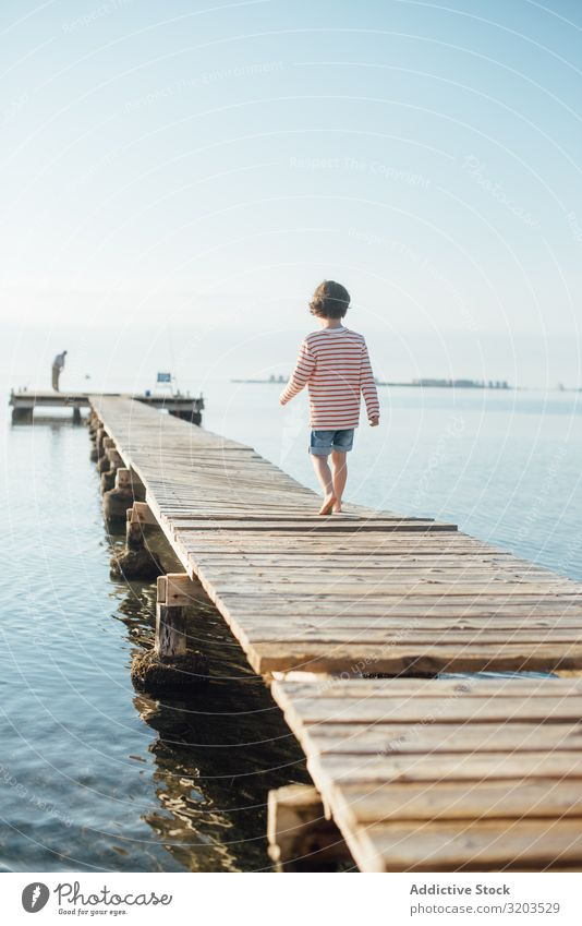 Lonely kid on pier in sunshine Boy (child) Jetty Walking Dream Child Summer Sunlight Vacation & Travel Infancy Water Nature Leisure and hobbies Trip Intellect