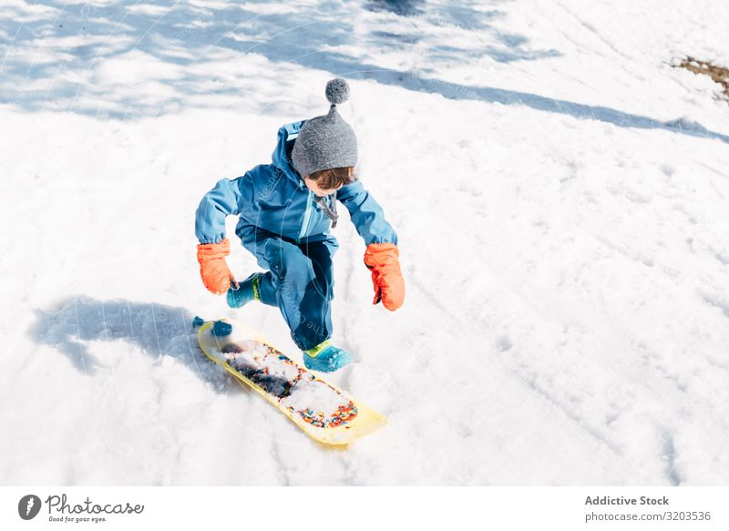 Kid jumping on board riding down snowy mountain Boy (child) Board Snow Slide Speed Small Winter Ride Sports Downward Action Relaxation Playful Jump Joy