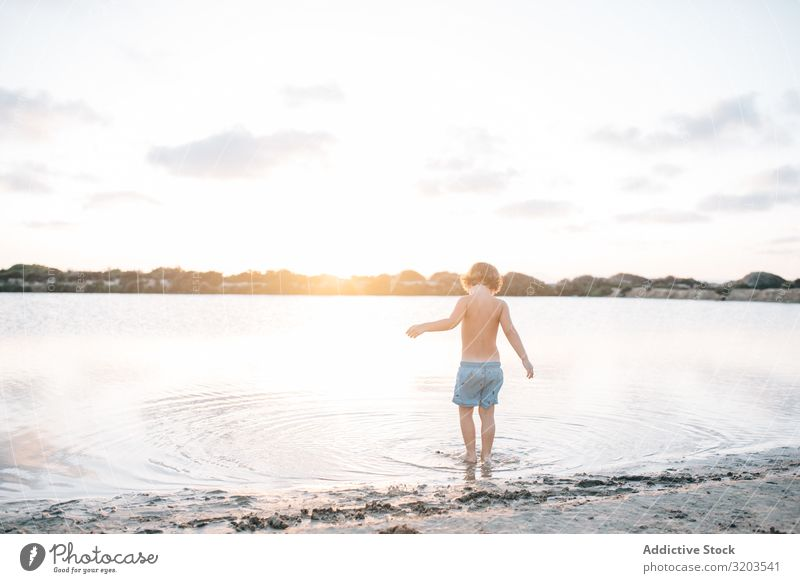 Boy walking in water of lake Boy (child) Beach Summer explore Water Walking Child Sunset Infancy Leisure and hobbies Vacation & Travel Bright Dream Loneliness