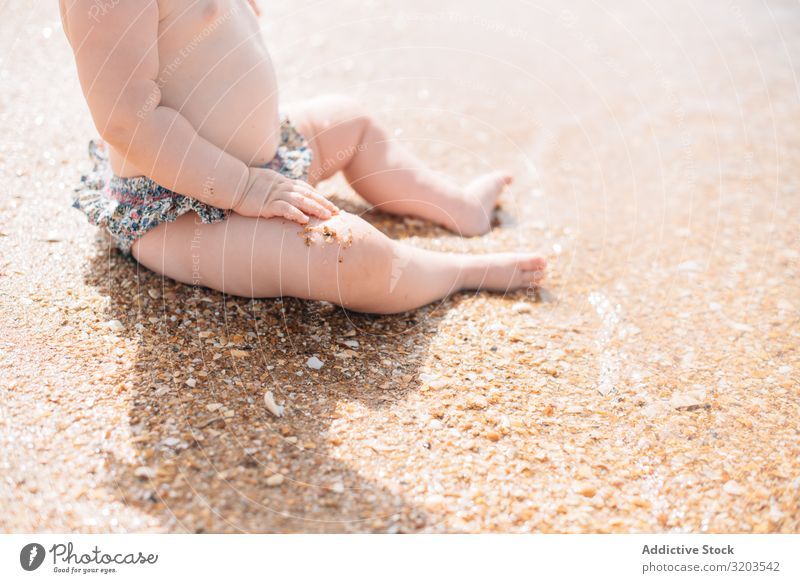 Crop view of anonymous cute baby sitting on beach Baby Beach Delightful Sand Wave Cute Summer Coast Leisure and hobbies Joy Child Vacation & Travel Strange Sun
