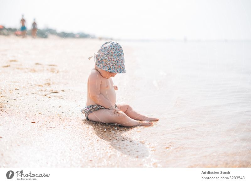 Cute baby sitting on beach Baby Beach Delightful Sand Wave Summer Coast Leisure and hobbies Joy Child Vacation & Travel Strange Sun Ocean Toddler Tropical Small