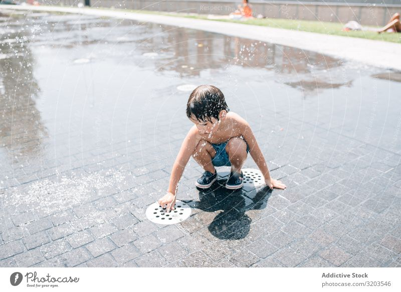 Kid standing in jet of fountain on street Boy (child) Fountain Street Jet Summer Float in the water Stream Water Park Joy Vacation & Travel Town Stand Fresh
