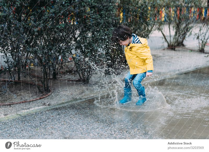 Happy kid jumping on puddle Boy (child) Puddle Jump Joy Street gumboots Wet Water Child Playful Infancy Autumn Weather Nature Rubber Playing Raincoat
