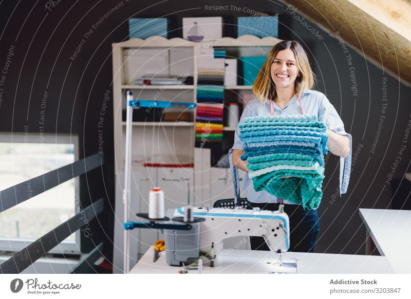 Cheerful seamstress with blue fabric Sewing Smiling Cloth Portrait photograph Accumulation Workshop Craft (trade) Woman Adults machine Equipment Tool