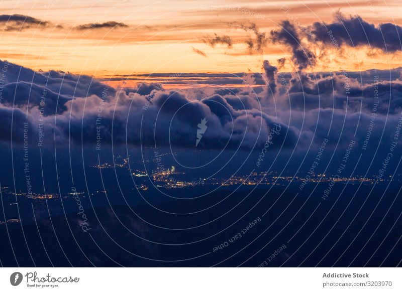 View of glowing city below clouds in sunset Landscape Sunset Clouds City terrain Mountain Valley Remote Sky Nature Dark Haze Picturesque Beautiful Vantage point