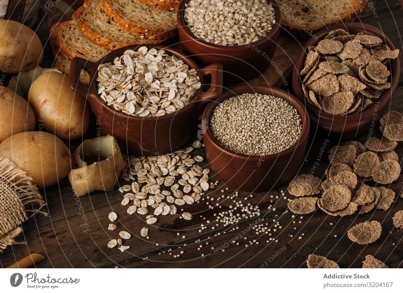 Wholegrain food and freshly baked rye bread on table Bread Potatoes oatmeal Cereals Meal Rye porridge appetizing Tasty dietary Seeds Fresh Ingredients Nutrition
