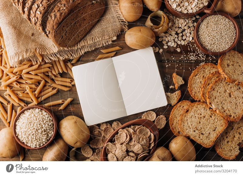 Wholegrain food and freshly baked rye bread on table Bread Potatoes oatmeal Cereals Meal Rye porridge Notebook appetizing Tasty dietary Seeds Fresh Ingredients