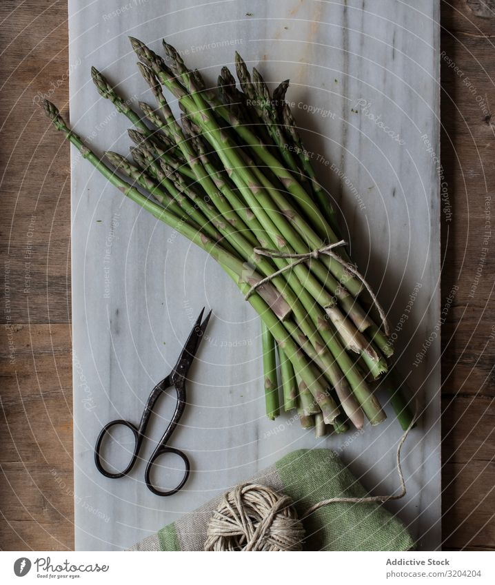 Arrangement of twine and asparagus on board Asparagus String Rustic Fresh Green Cooking Vegetable bunch Raw Healthy Nutrition Vegetarian diet Ingredients Diet