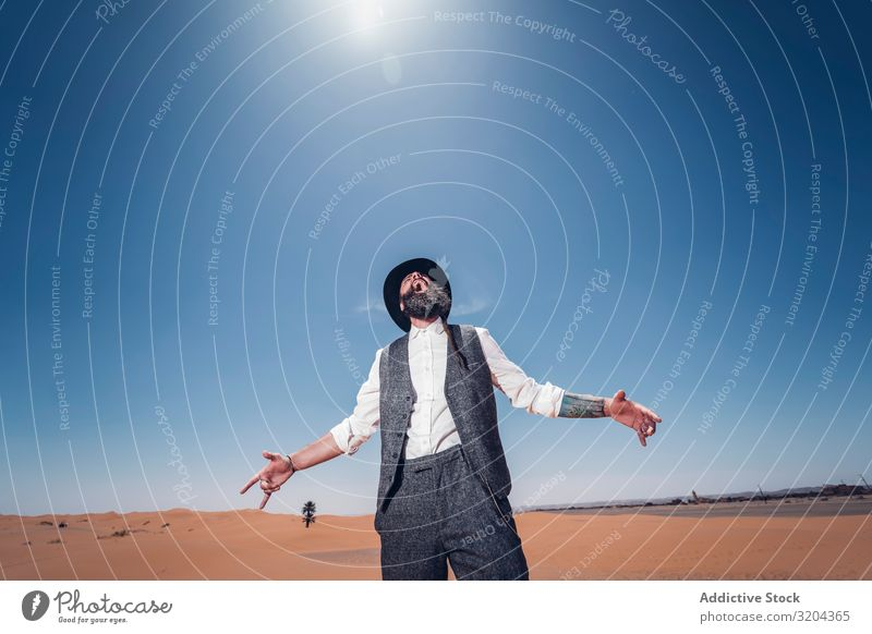 Bearded cowboy in desert Cowboy Desert Costume Time bearded Man Sand Sky Blue Sunbeam Day Hat Retro Adults Dry arid terrain Landscape Guy Nature Western Style