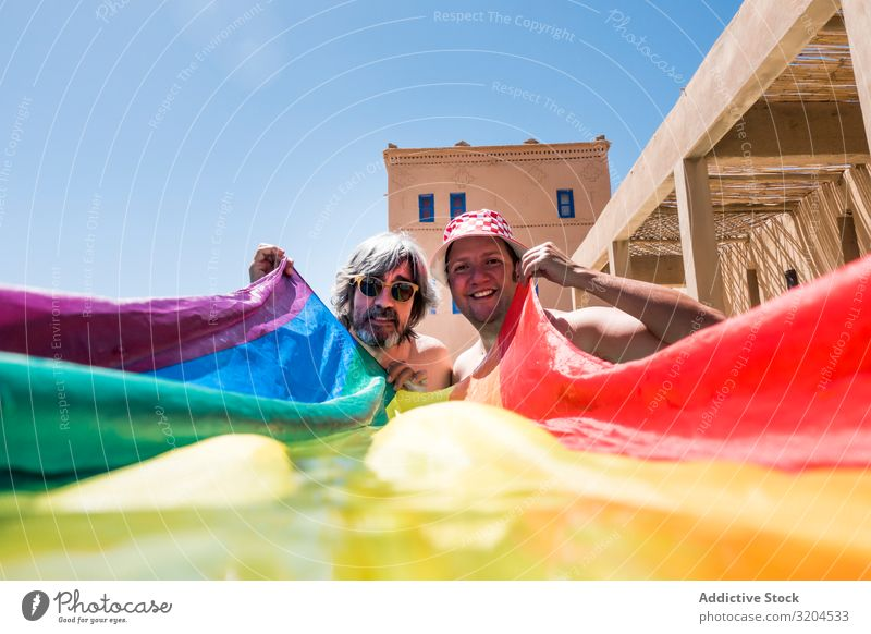 Happy gay couple in swimming pool Homosexual Couple Swimming pool lgbt Flag Overweight Together Love Resort Vacation & Travel Water Man hiding Cover Rainbow