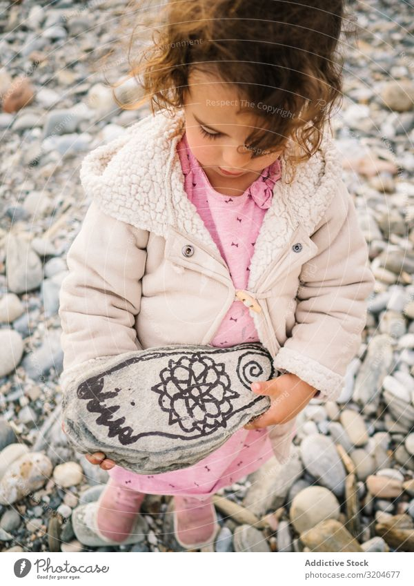 Girl holding painted stone while playing on beach Playing Stone Beach Painted Toddler Interest Cute Infancy seaside Intellect Creativity Serene Coast