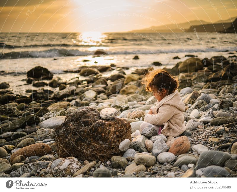 Girl sitting on rocky beach Playing Stone Sit Beach Toddler Interest Cute Infancy seaside Intellect Creativity Serene Coast Vacation & Travel Action Child