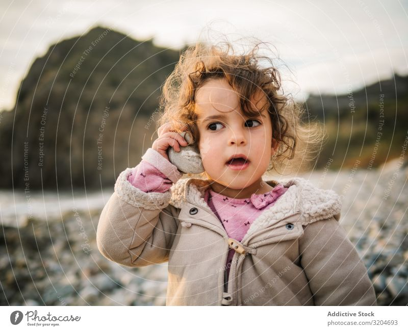 Toddler girl playing with seashell on beach Girl Playing Beach Child attention rapt Portrait photograph Listening conch Resting Nature Interest Discovery