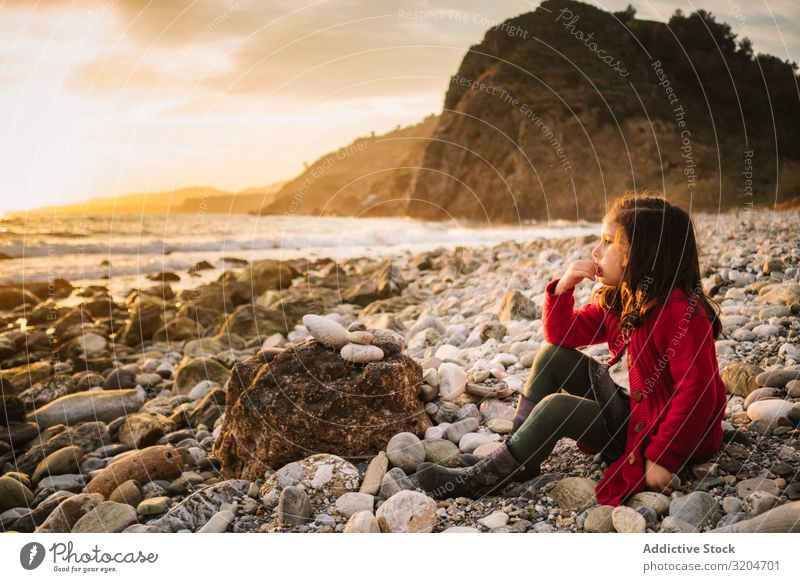 Dreamy girl resting on beach at sunset Girl Child Resting Beach Sunset Pensive admiring Calm seaside Woman Beautiful Relaxation Leisure and hobbies To enjoy