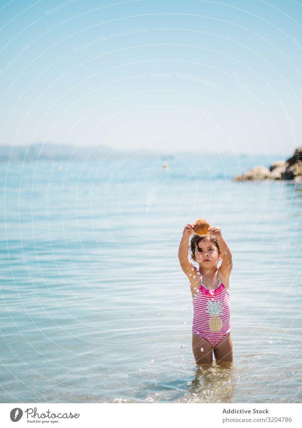 Cute girl playing in water of seaside Girl Water Playing seashell Toddler Delightful Ocean swimming suit Warmth Beach Sunbeam Infancy Swimming & Bathing