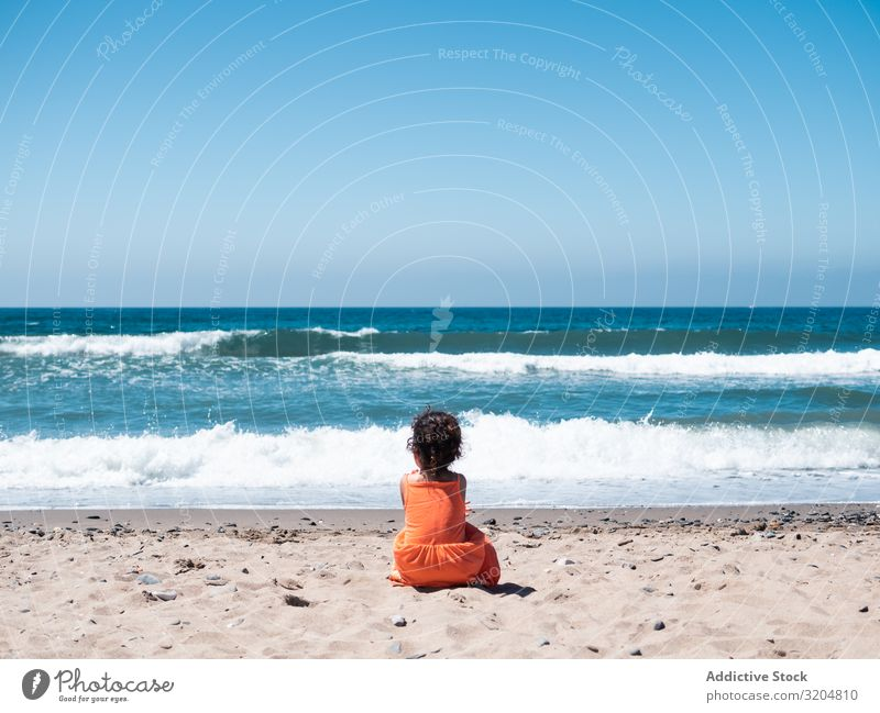 Little girl sitting on beach and admiring view Girl Beach Child Sit Vantage point seaside Sand Ocean Sky Small Woman Orange Dress Looking Beautiful Summer Wave