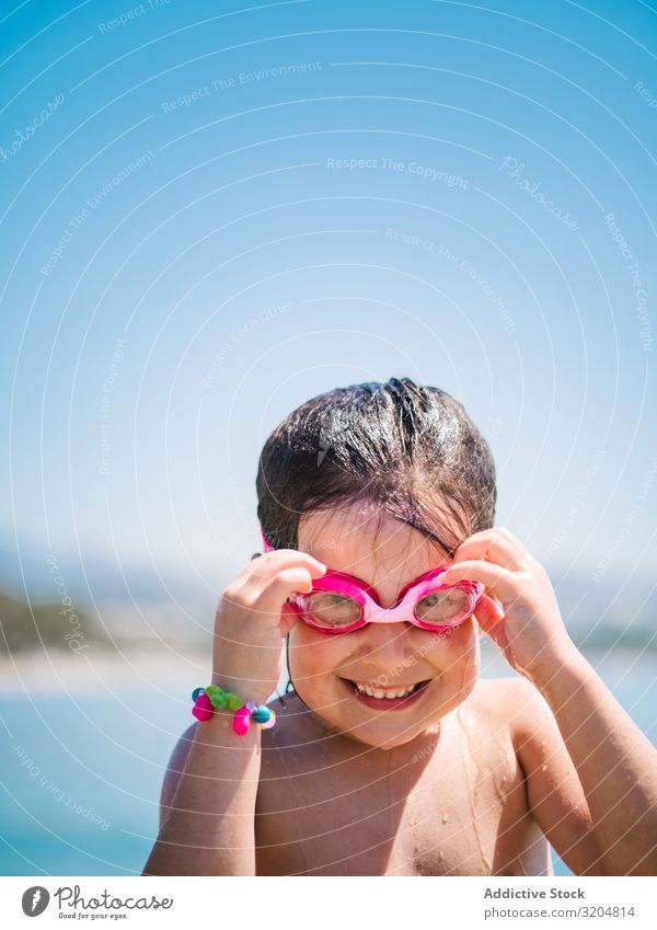 Cheerful girl in goggles after swimming in sea Girl Skiing goggles Ocean Cute Smiling Child taking off Blue sky Woman Summer Happy Leisure and hobbies