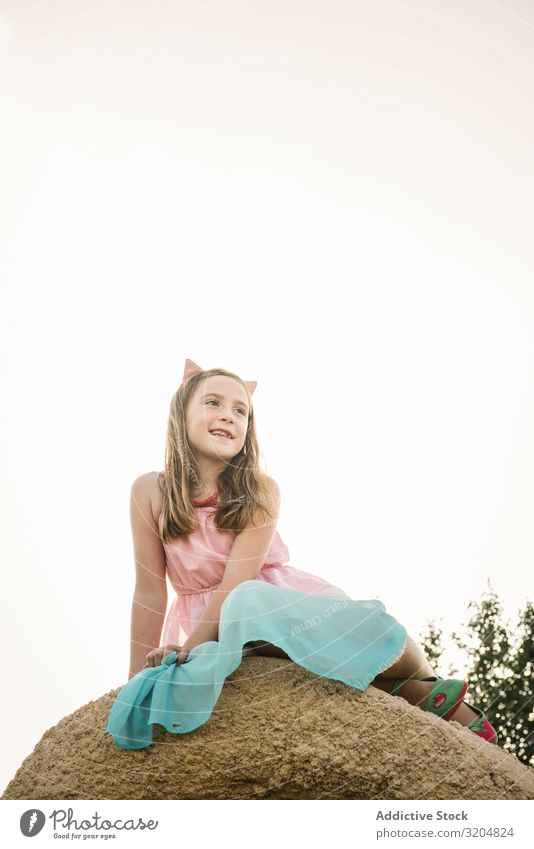 Dreamy cute girl sitting on rock Girl Nature Child Summer Infancy Cute Dress Beautiful Beauty Photography Sit Contemporary explore Innocent Smiling Rock Sky