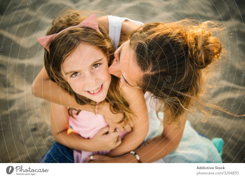 Woman with daughter on sunny beach Daughter Beach Love Embrace Family & Relations Summer Mother Together Girl Sand Parents Vacation & Travel Bonding Contentment