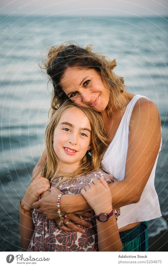 Beautiful mother and daughter embracing on beach Woman Daughter Beach Embrace Love Happy Beauty Photography Mother Family & Relations Together Child Style Ocean