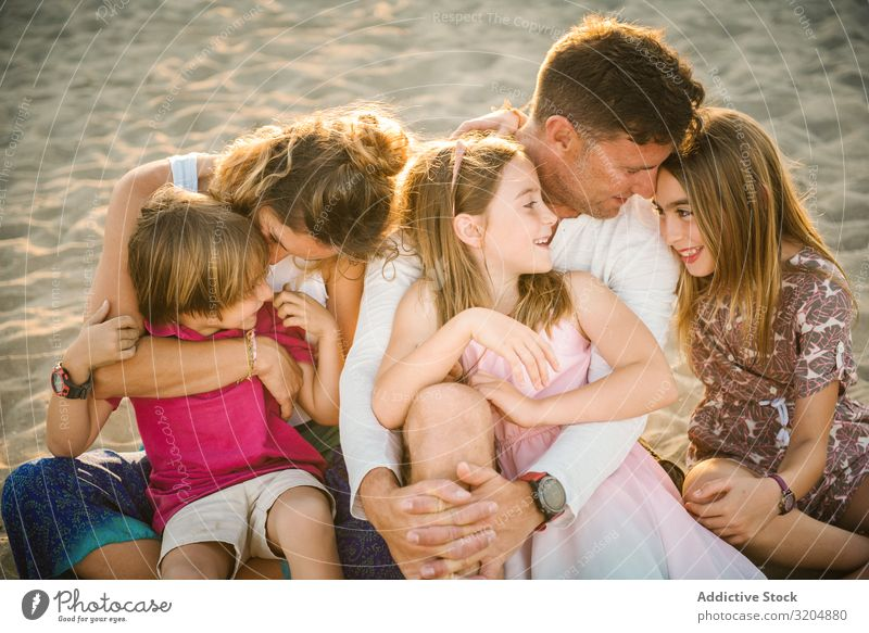 Beautiful happy family with playful children on beach Family & Relations Love Beach Happy Parents Child Group sibling Summer Vacation & Travel Sit Embrace Sand