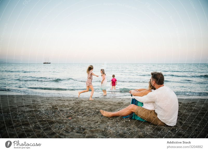 Beautiful happy family with children on beach Family & Relations Love Beach Happy Parents Child Group sibling Summer Vacation & Travel Sit Embrace Sand Playful