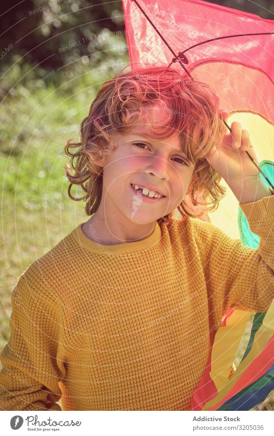 Cheerful boy holding colorful kite Boy (child) Kite Joy Teeth missing Infancy Playing Child Small Man Human being Happy Curly Delightful Beautiful Playful Cute