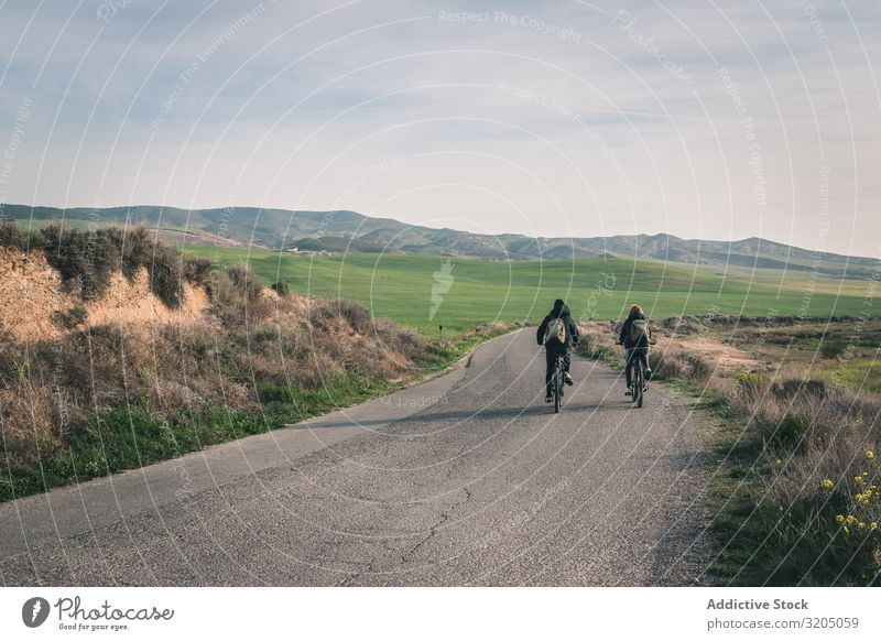 Men riding bicycles on road in desert hills Man Bicycle Street Desert Hill Landscape Sand Stone Plant Trip Dry Nature Sky Vacation & Travel Hot Destination